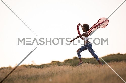Young beautiful black girl laughs and dances outdoors with a scarf in her hands in a meadow during sunset