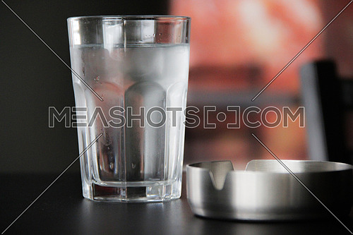 A glass of cold water and an ashtray on a wooden table