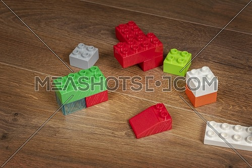 nice view on colorful toy bricks on a brown wooden background. Toys in the table