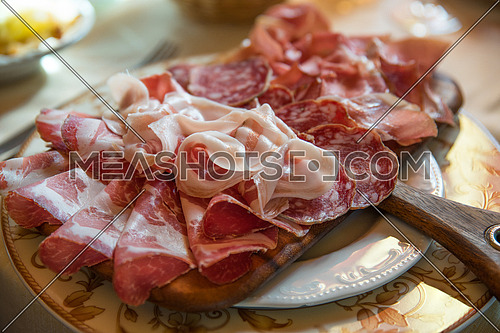 Typical various italian salami, servided on plate at restaurant.
