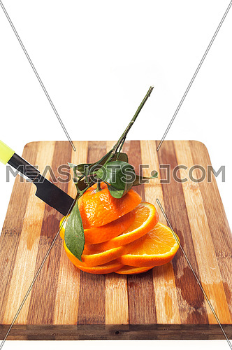 fresh orange sliced on cuting board over white
