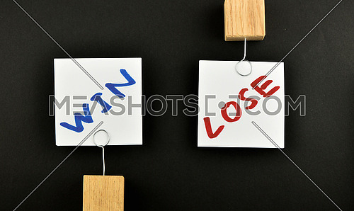 win lose, two white paper notes with wooden holders in different directions isolated on black paper background for presentation