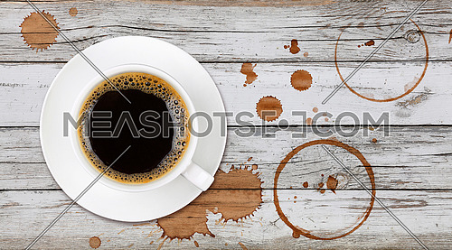 Brown cup full of black coffee on saucer, with ring coffee stains and drops on white painted wooden table background, elevated top view, directly above