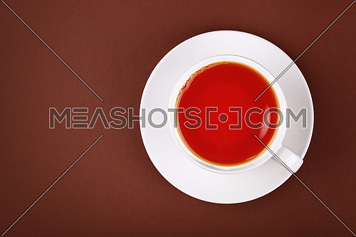 Close up white cup full of red black tea on porcelain saucer over brown paper background, close up, elevated top view, directly above