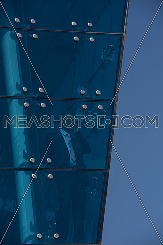 Outdoor shoot showing a senior male business executive though glass front of a modern corporate building showing blue sky
