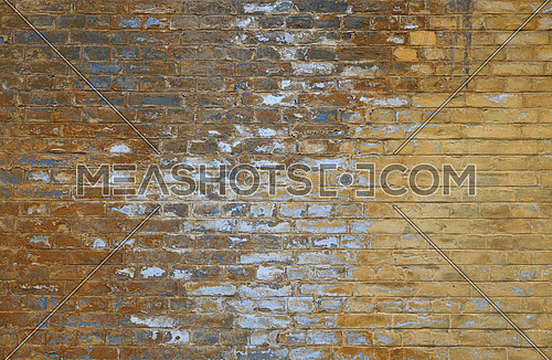 Old grunge vintage yellow painted brick wall with blue and white paint stains and dirt faded background