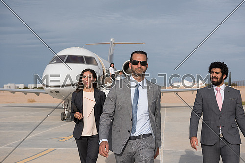 young successful businessman walking with his Arab business partner in front of private airplane