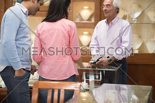 Young middle eastern happy couple enjoying while buying in a luxury jewelry store