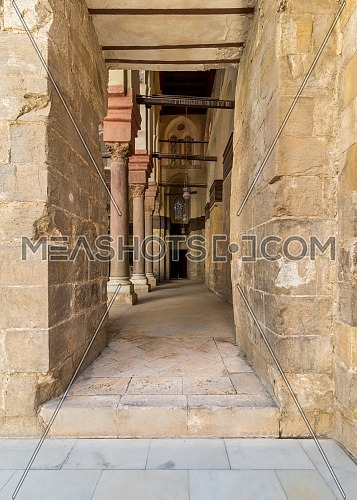 Passage at Sultan Qalawun Mosque with stone columns, colored stained glass windows and wooden door, Cairo, Egypt