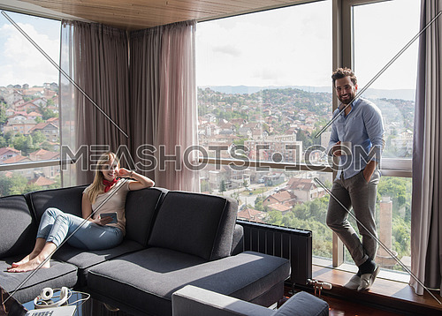Young couple relaxing at  home using tablet computer reading in the living room near the window on the sofa couch.