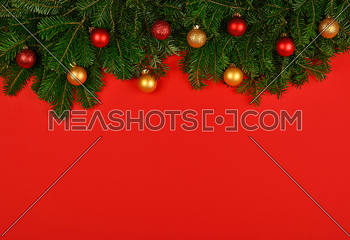 Close up fresh green spruce or pine Christmas tree branches decorated with cones, golden balls and baubles, over red background with copy space