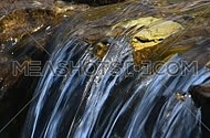 Brook water stream with small rift in day time, focus in