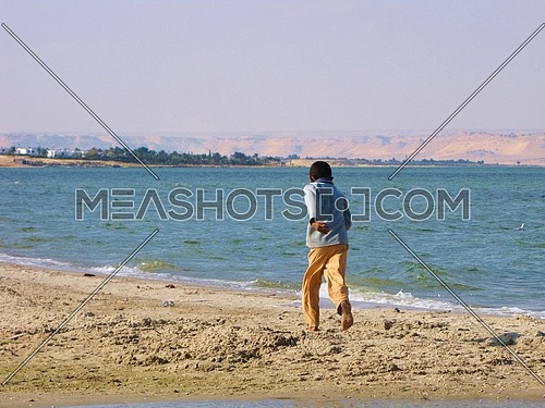 A boy running away by the sea shore
