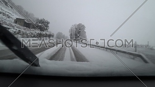 Car driving through winter snow storm on snow-covered mountain pass road.