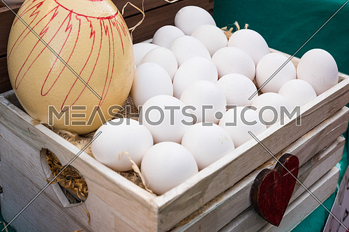 White chicken eggs leaning on straw in wooden basket at market,outdoor.