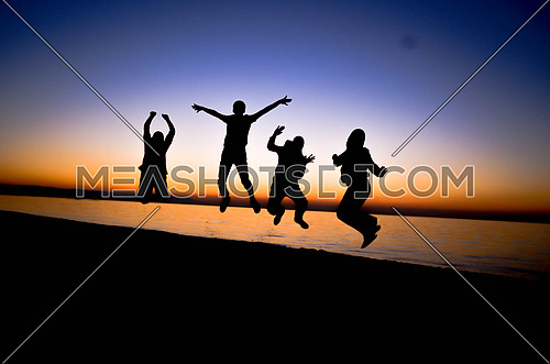 four friends jumping at the beach during sunset magic hour