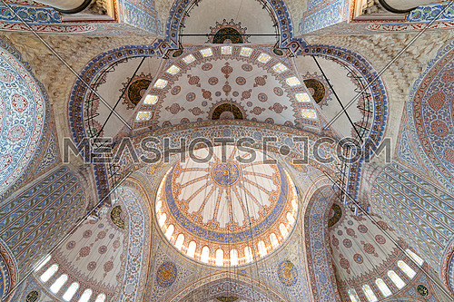 Decorated ceiling of Sultan Ahmet mosque (blue mosque) with huge pillars, domes, arches and stained glass windows, Istanbul, Turkey