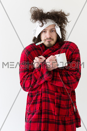 young Man with flu and fever wrapped holding cup of healing tea isolated over white