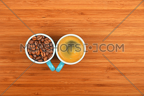 Two blue coffee cups of espresso and roasted Arabica beans over wooden bamboo board background