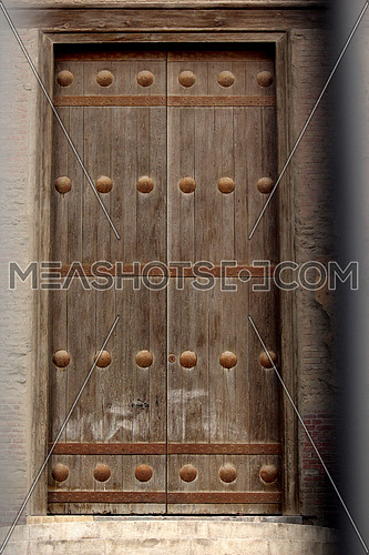 a photo of a vintage wooden door from inside Ahmed bin Tolon Mosque in old Cairo, Egypt showing the style of Architecture used at that time  and a monumental door