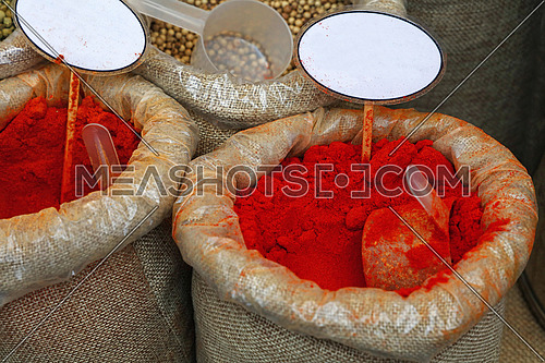 Close up several canvas bags of assorted spices, red paprika, white peppercorns, with copy space of blank price tags on retail display of market stall, high angle view