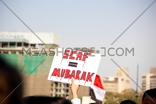 a hand holding a sign in a protest SCAF = Mubarak