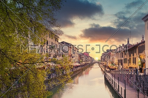 Naviglio Grande canal at sunset,on the sides of the canal the typical bars, restaurants and typical shops of the