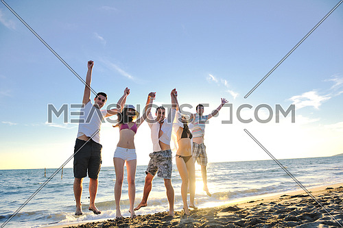 happy young friends group have fun and celebrate while jumping and running on the beach at the sunset