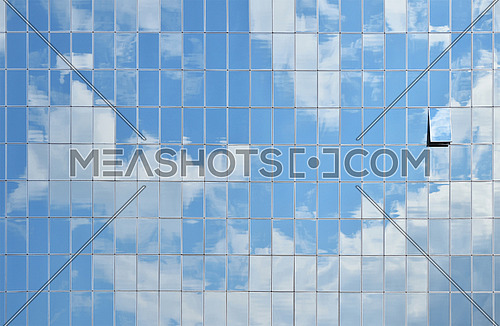 Cloudy blue sky reflection in glass windows of office business building, side view