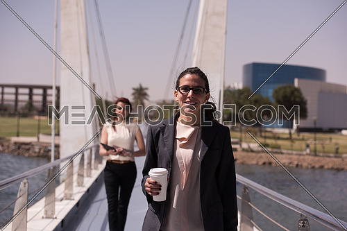 business women walking across a modern footbridge at early mornig while drinking coffee