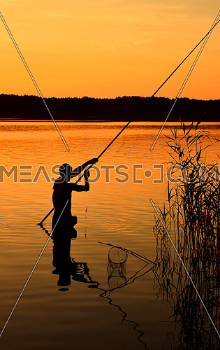 Dark silhouette of one man standing in water with fishing rod over vivid orange sunset sky and lake background, rear view