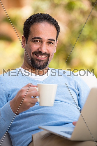 young Middle Eastern man enjoying a coffee in the garden sunny summer morning