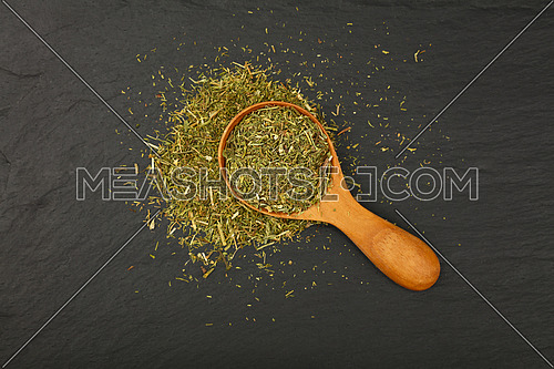 Close up one wooden scoop spoon full of green dried herbs, dill or marjoram on background of black slate board, elevated top view, directly above