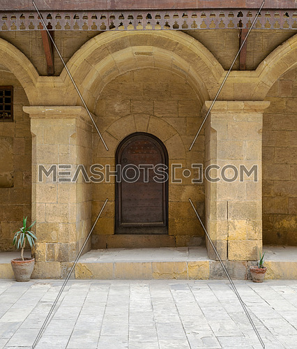 Wooden decorated door framed by arched bricks stone wall at caravansary (Wikala) of Bazaraa, suited in Tombakshia street, Al Gamalia district, Medieval Cairo, Egypt