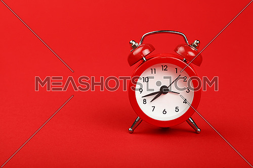One small metal retro alarm clock with red bells over red paper background, close up, low angle front view
