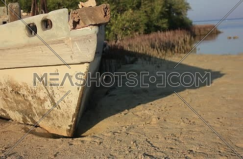 Close Shot for an Old wodden boat on the seashore with green tress in background at Wadi Lahmi at Day - 5D