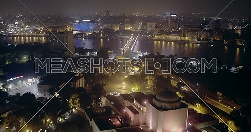 Aerial shot flying backward Cairo opera house showing the river Nile and Kasr AL Nile Bridge at night