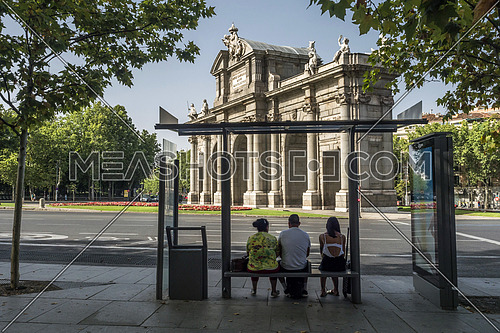 Madrid, Spain - August 4 2018:  Alcala Gate or Puerta de Alcala, Three travelers waiting at the bus stop, is a monument in the Plaza de la Independencia in Madrid, Spain