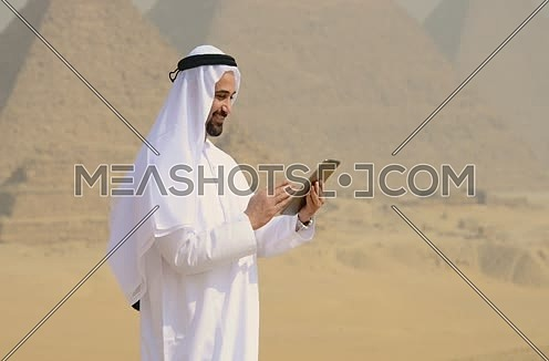 Emiratie man at the pyramids working on tablet