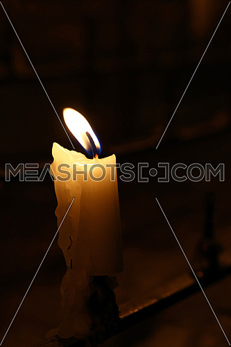 One white candle with melting wax burning in dark church, close up, high angle view