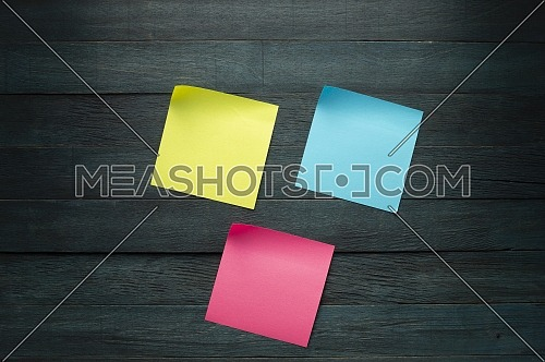 Empty color office paper for notice with curled corners on blue rustic board. Free copy space for text