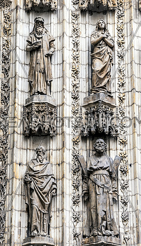 Sevilla, SPAIN - September 9, 2017: Detail of the statues of saints sculpted in stone at the door of the Assumption of the cathedral of Seville, Spain