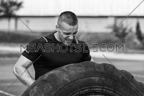 Young Man Turning Tire Over - Bodybuilding Exercises Truck Tire