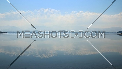 Animated cinemagraph of scenic cloudscape and blue cloudy sky reflection in tranquil mountain lake waterfront
