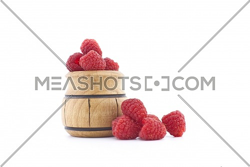 Pile of red ripe raspberry berries and a small wooden pot isolated on white background