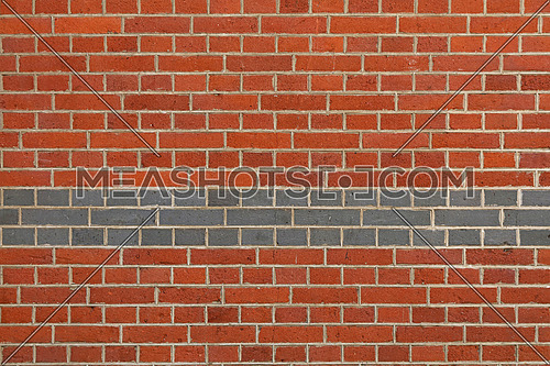 Rough red brown brick wall background texture with three rows of grey brick, close up, side view