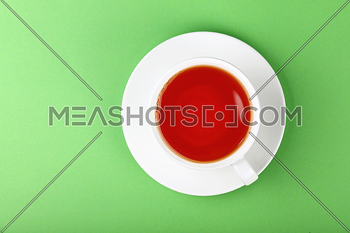 Close up one full white cup of black or red fruit infusion tea on saucer over pastel green paper background, elevated top view, directly above