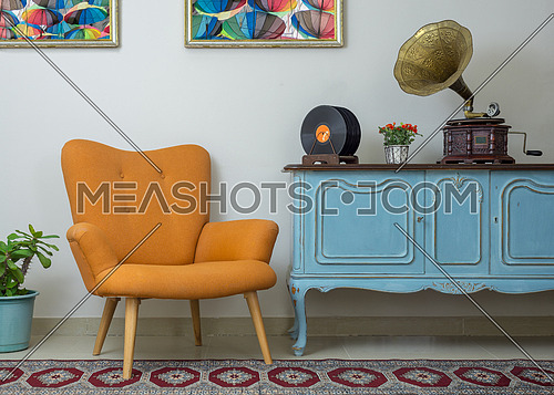 Vintage interior of retro orange armchair, vintage wooden light blue sideboard, old phonograph (gramophone), vinyl records on background of beige wall, tiled porcelain floor, and red carpet