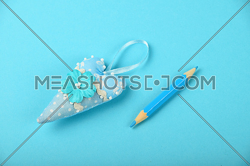 One small textile heart with mulberry paper flower and ribbon on tender blue background
