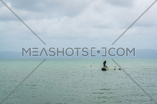 Fisherman on the small boat fishing with the net on Los Haitises National Park,peninsula Samana,Dominican republic.